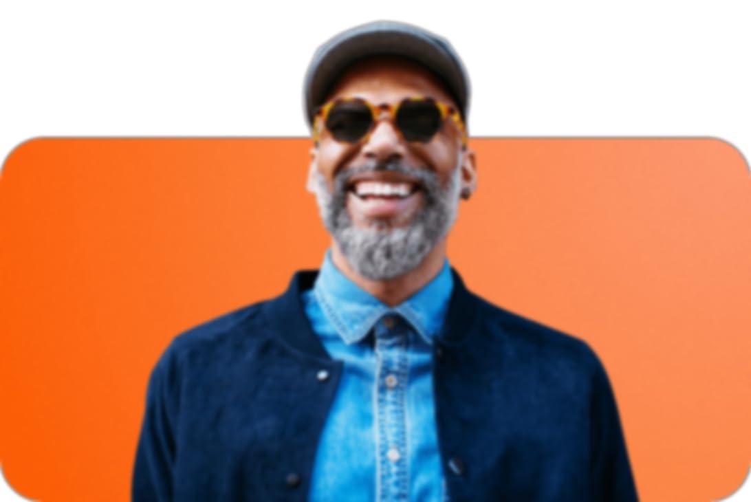 lachende man met pet en een zonnebril, gekleed in een spijkerblouse en een donkerblauw jack