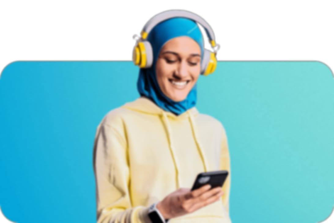 vrouw met een koptelefoon op en een smartwatch om die naar haar telefoon kijkt en een blauwe hijab en pastelkleurige hoodie draagt