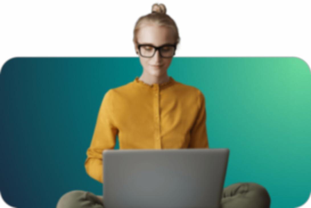 mujer sentada con las piernas cruzadas y un ordenador en el regazo