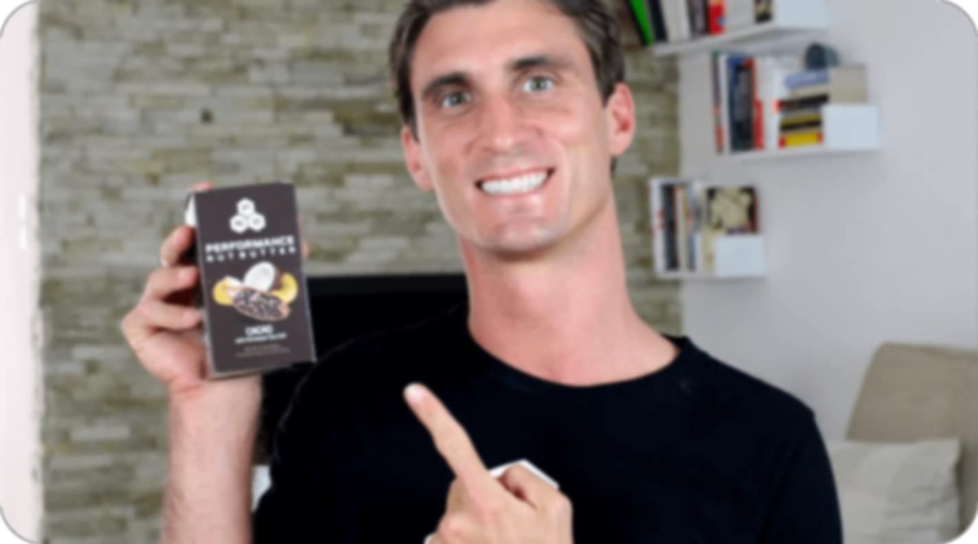 person pointing to a black box of butter nut butter with one finger while smiling
