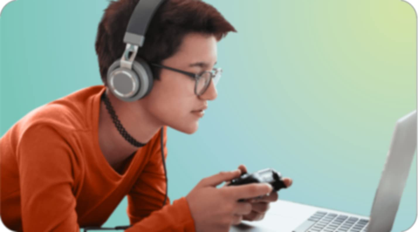 Una persona con lentes, una banda para el cuello, y audífonos, está jugando videojuegos usando un control y su computadora portátil. La persona está inclinada hacia la computadora portátil.