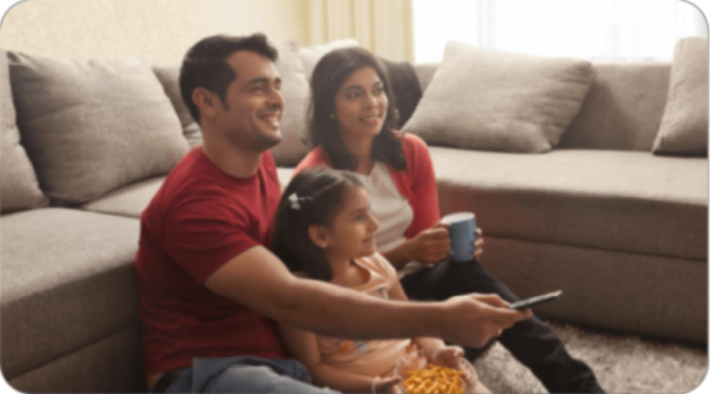 Una familia sentada en el piso frente a su sofá, mientras uno de los progenitores tiene un control remoto en la mano. El niño está tendido en el regazo de esa persona y el otro progenitor está sentado cerca de los otros dos, con una taza de café en la mano. Todos están viendo la televisión.
