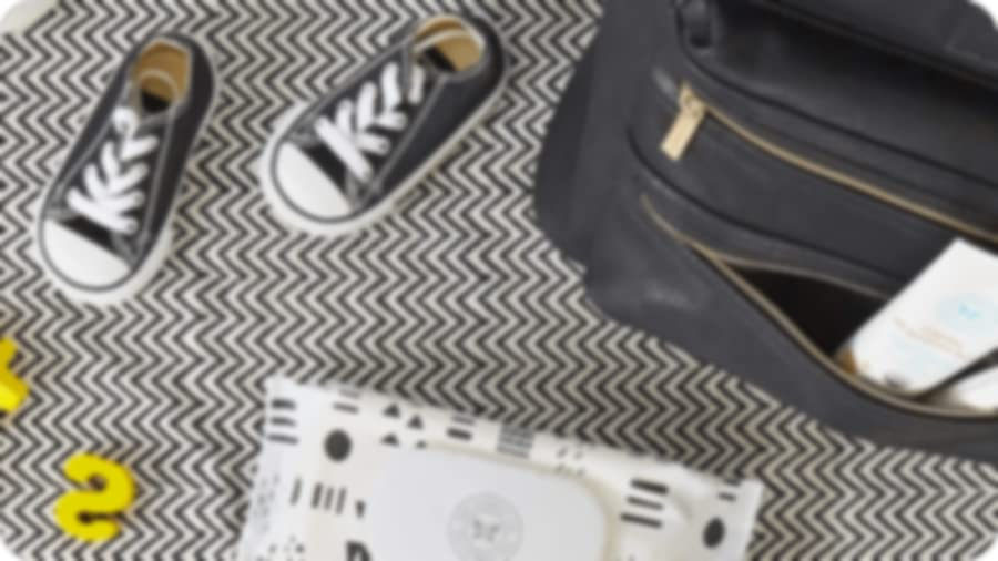 Some baby sneakers next to a baby bag and honest beauty wipes