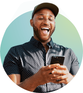 person laughing while looking at their phone with a hat and polka-dot button-up top on