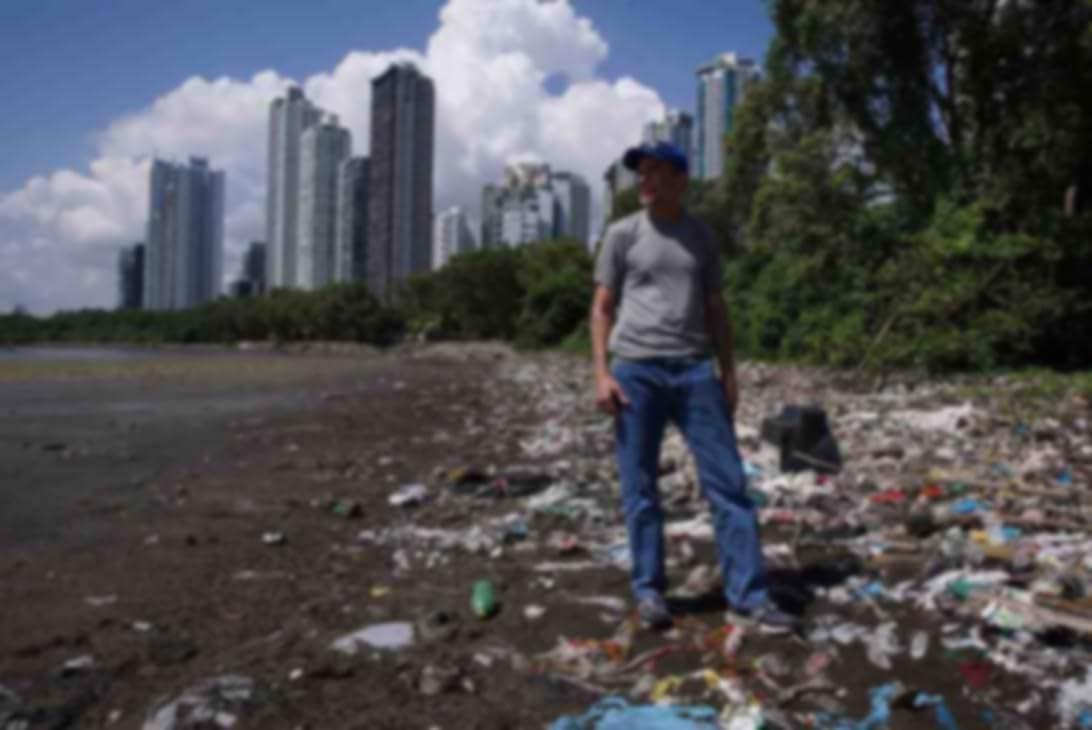 Homme debout sur une plage couverte de déchets plastiques.