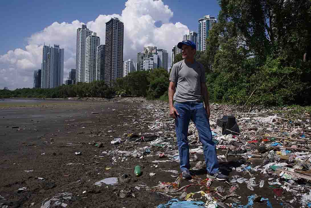 Man standing on a beach which is covered with plastic waste.