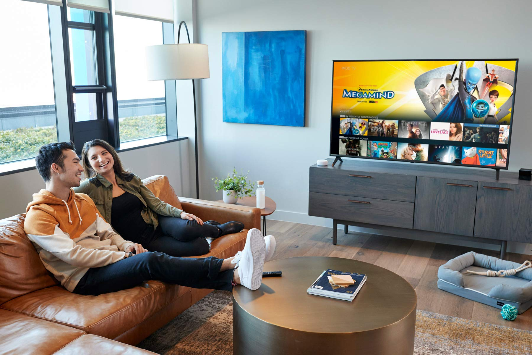A young man and a young woman laugh together while sitting on a couch in a living room with a TV in the background, which shows a movies selection screen.