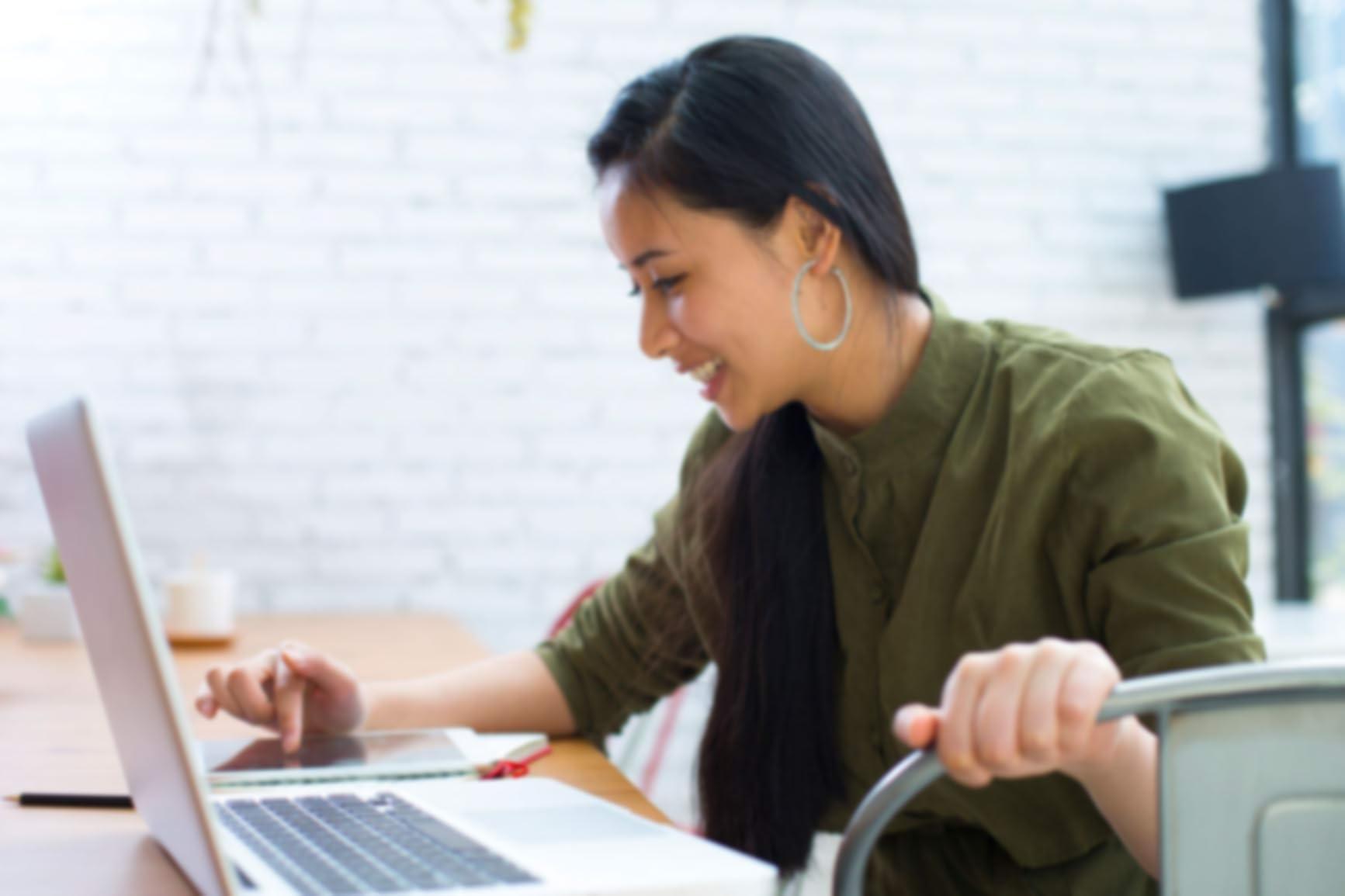 Une jeune femme, assise à une table avec un ordinateur portable, fait défiler l'écran de sa tablette.
