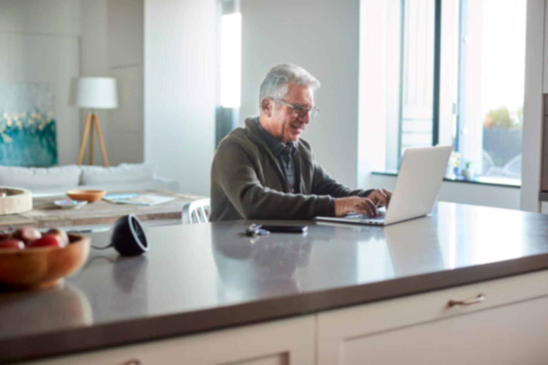 Un hombre mayor está sentado en el mostrador de la cocina mientras escribe en una computadora portátil.