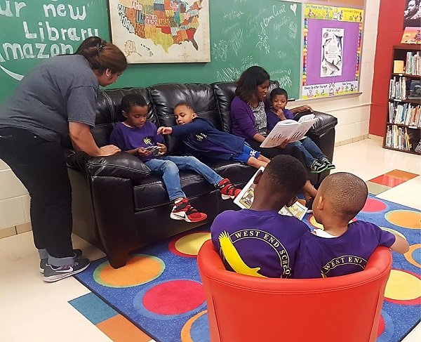 Amazonians read to students after library makeover.