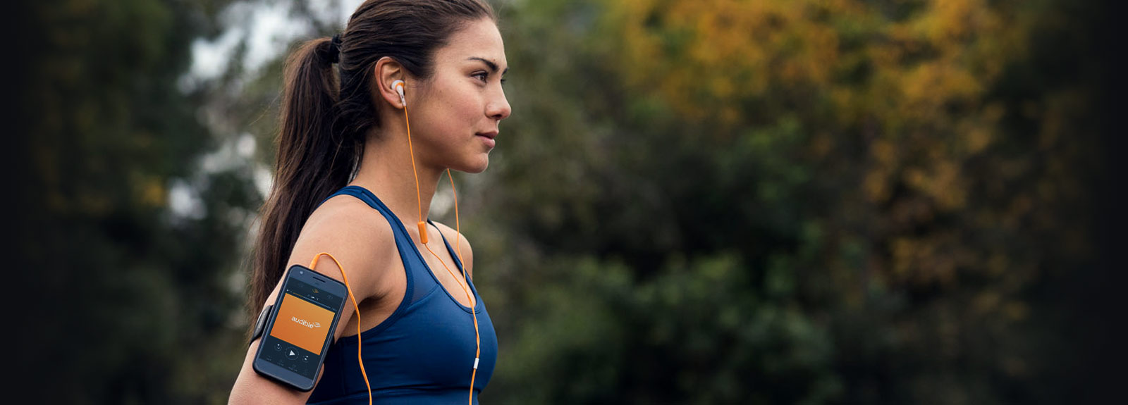 Girl in blue shirt listening to an audiobook with her smartphone while exercising.