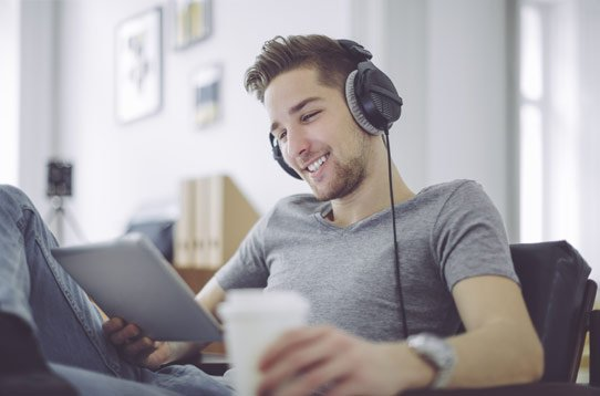 Guy with headphones sitting down and looking at a tablet