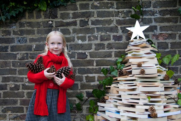 Girl with a Christmas tree made of books