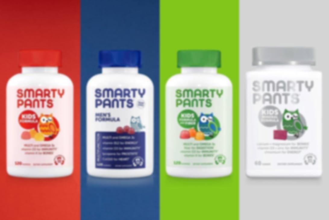 Cuatro paquetes de vitaminas SmartyPants clasificadas por los colores visibles en los tapones. Las vitaminas que se muestran son: fórmula para niños, fórmula para hombres, fórmula infantil con fibra, fórmula mineral para niños.