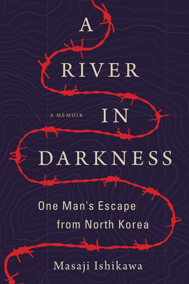 The book cover of A River in Darkness: One Man's Escape from North Korea by Masaji Ishikawa. Translated by Risa Kobayashi and Martin Brown. The cover shows a river of red barbed wire winding over a purple, topographical landscape.