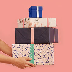 A hand holding a stack of wraped gifts