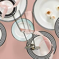 A pair of champagne flutes on top of plates with ribbon