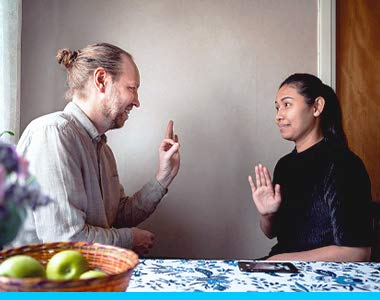 Two ASL signers are having a conversation, sitting by a kitchen table with a floral tablecloth and basket of apples on it.