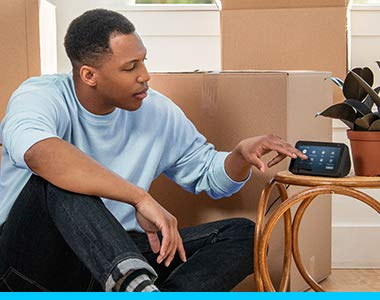 In a living room, next to moving boxes, a man sits on the floor and taps on the screen of an Echo Show device.