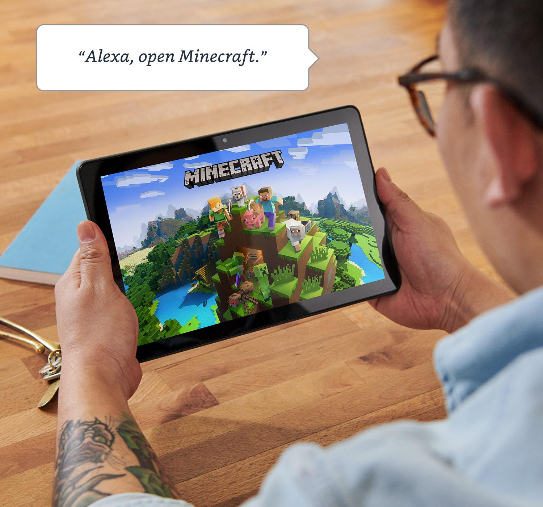 """""""Alexa, ouvre Minecraft.""""  Homme assis à table jouant à Minecraft sur Fire HD 10 Plus."""