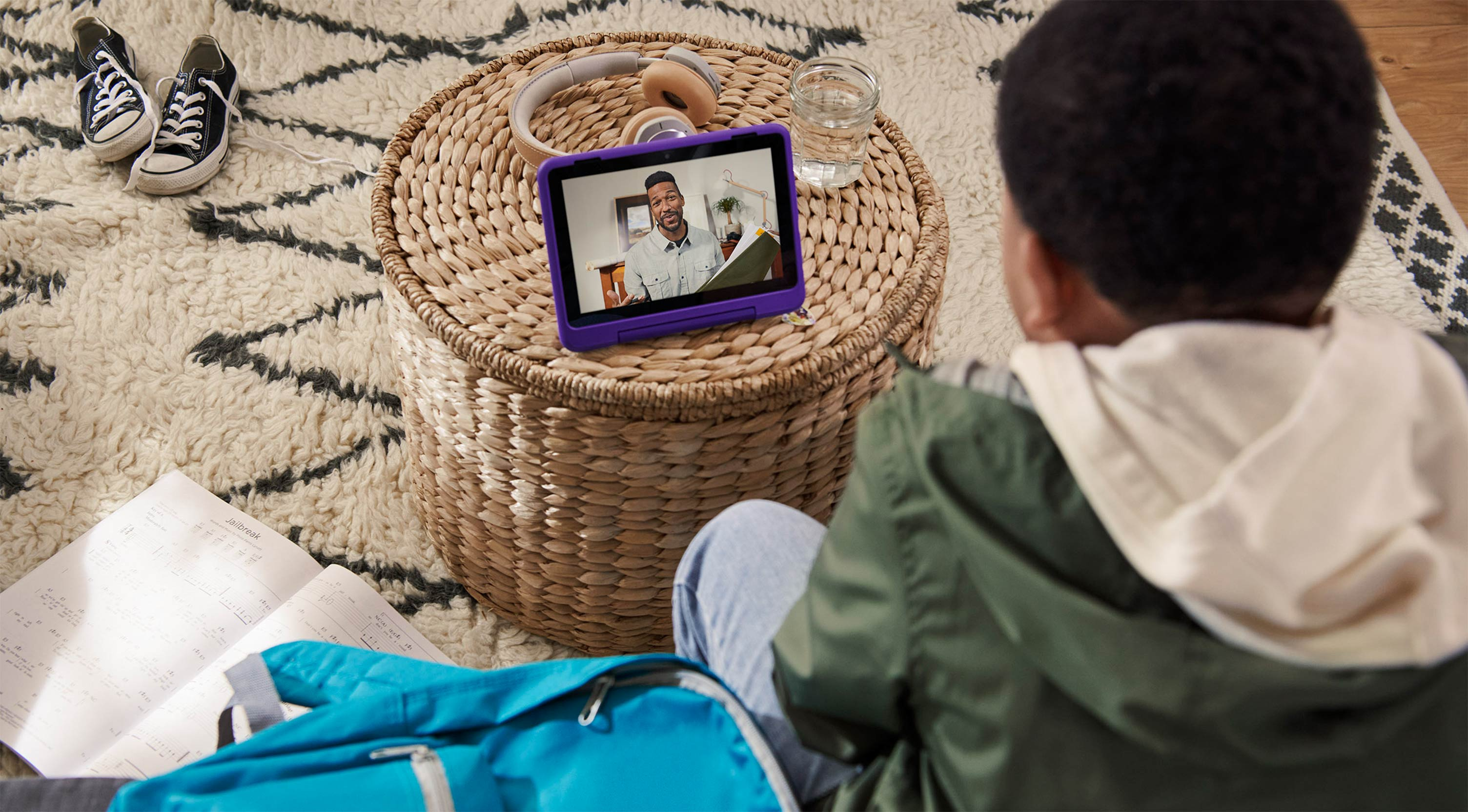 Male child seated on floor engaged in video call with adult via tablet.