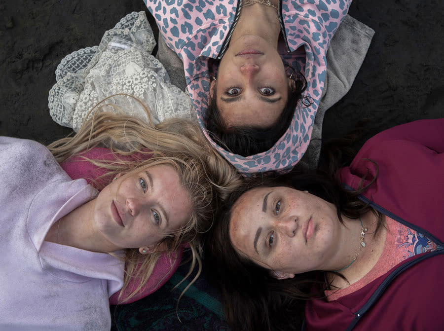 Three girls lay on their backs, arranged in a circle with their heads at the center, looking up at the camera with solemn looks on their faces.