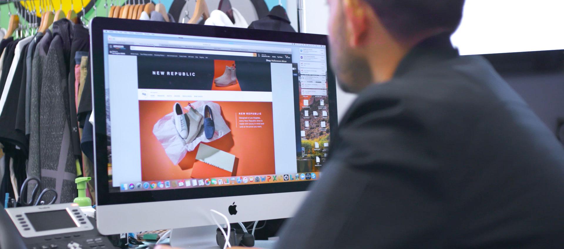 一位男士正看着电脑屏幕,上面显示时尚品牌 New Republic 在 amazon.com 平台的网上店铺