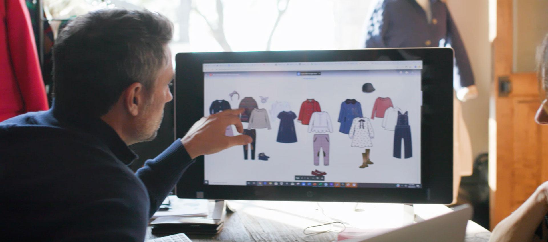 Ein Mann sieht sich Modeentwürfe auf einem Computer an