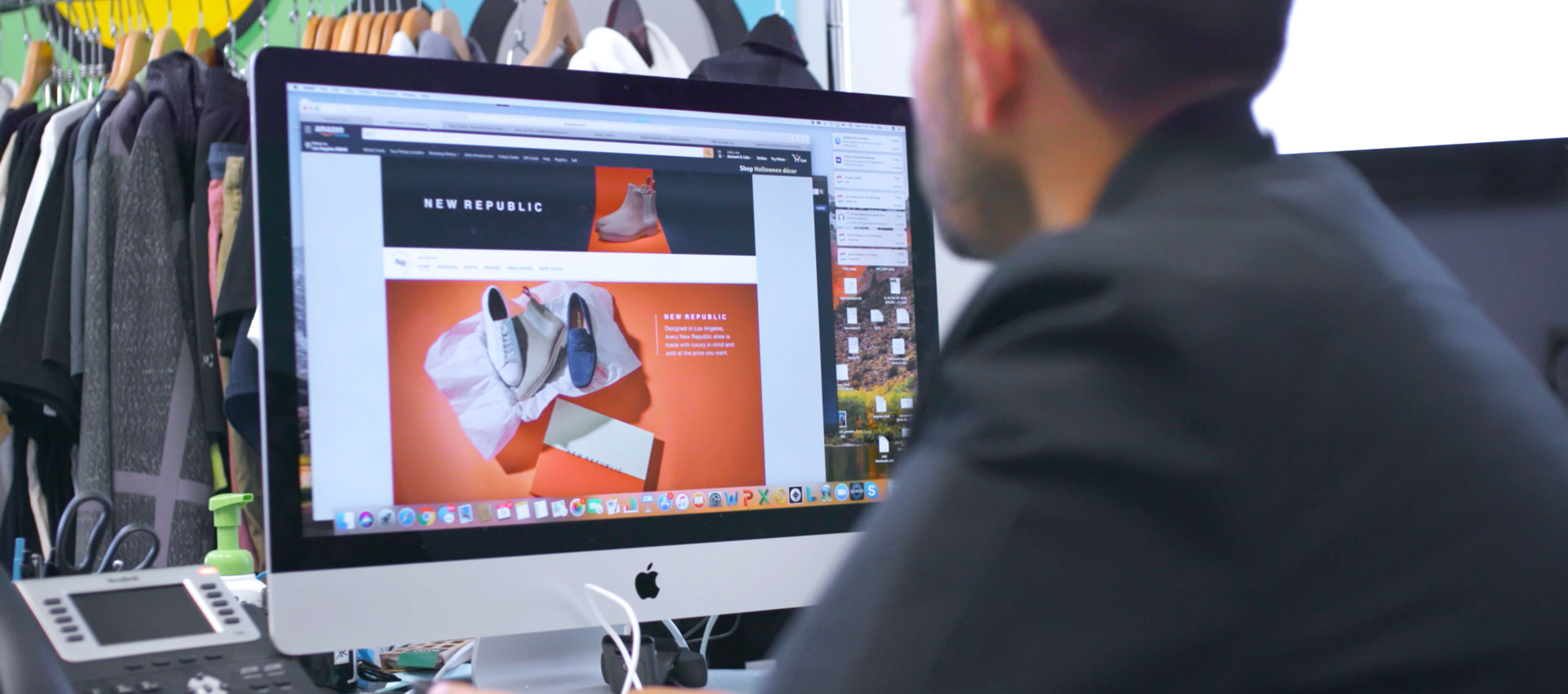 A man looking at a computer screen showing an online store on amazon.com for the fashion brand New Republic