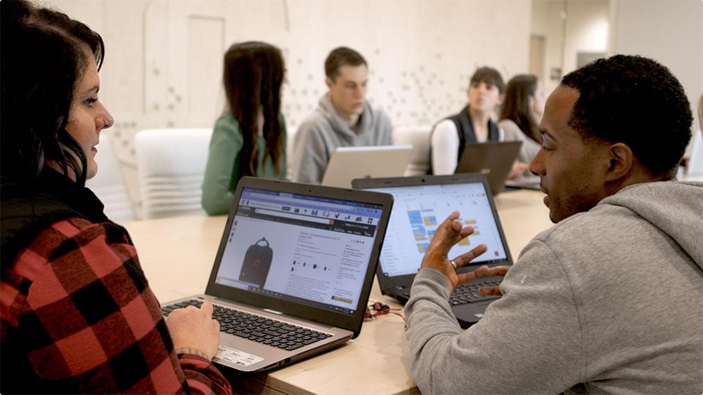两个使用笔记本电脑的人正在交谈