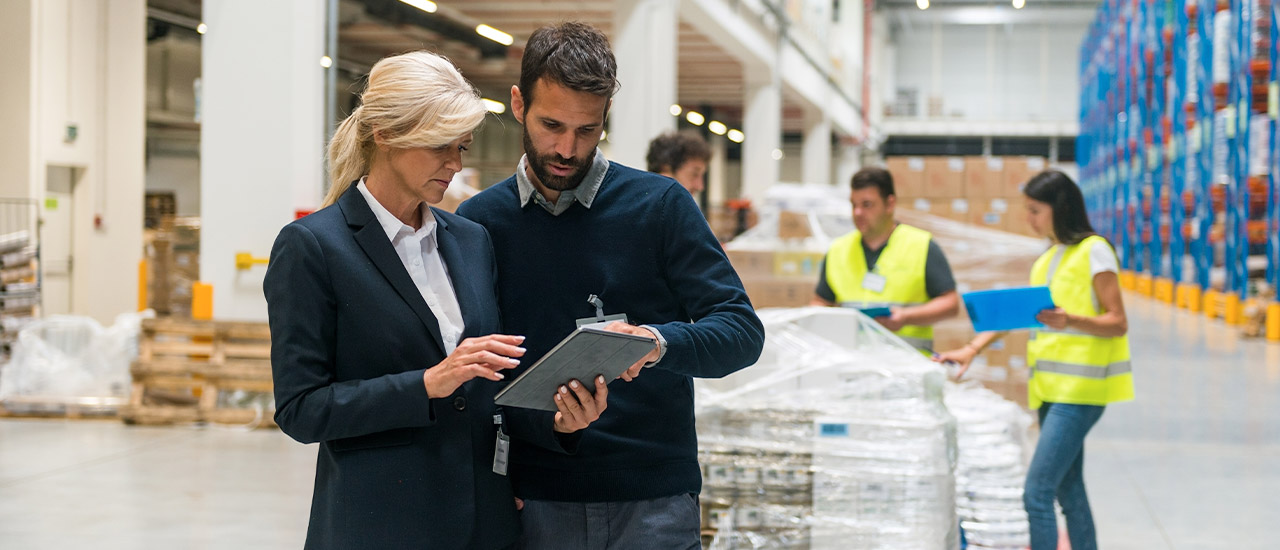 a man and a woman looking at a clipboard while standing in a warehouse