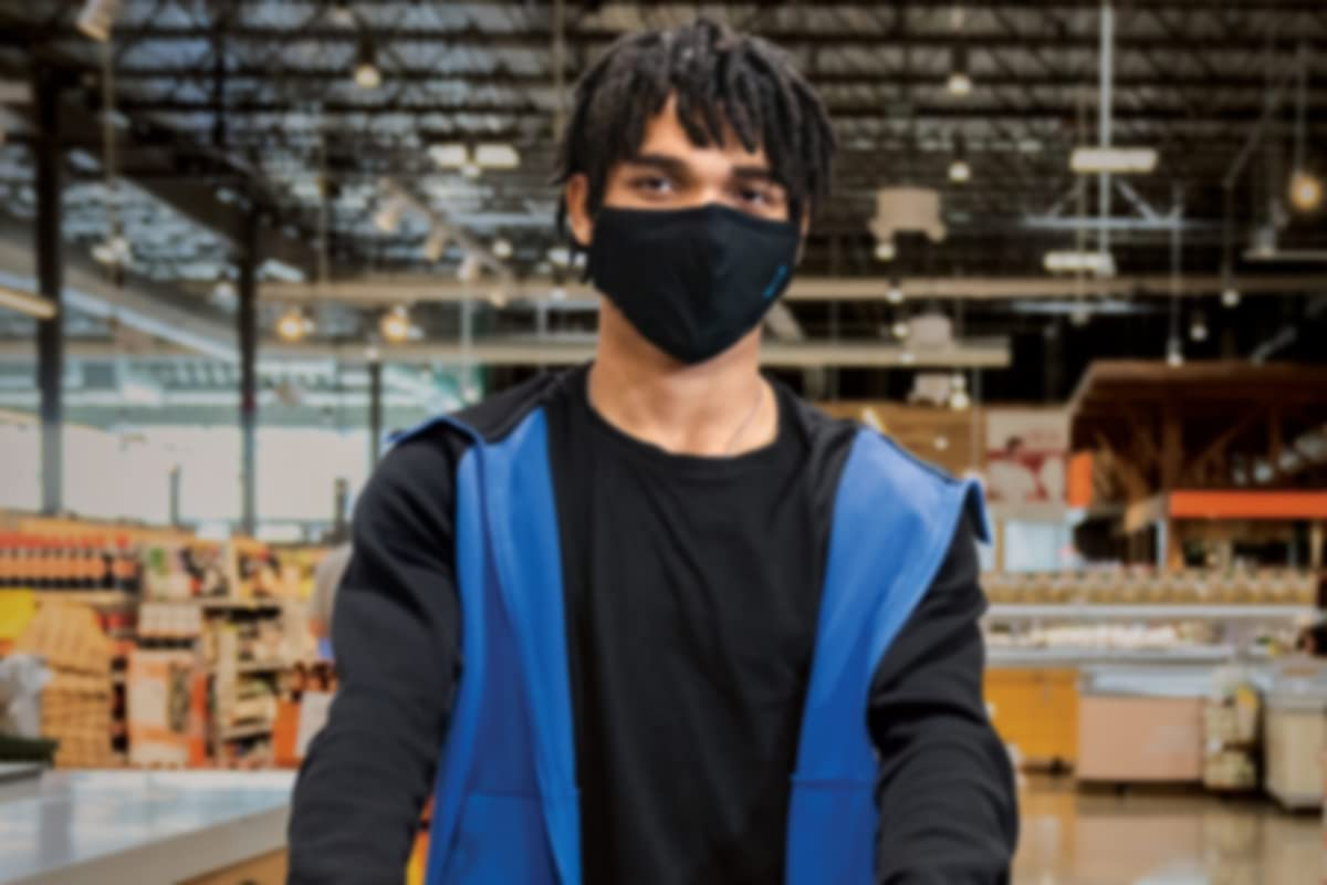 Amazon grocery fresh associate smiling with mask.