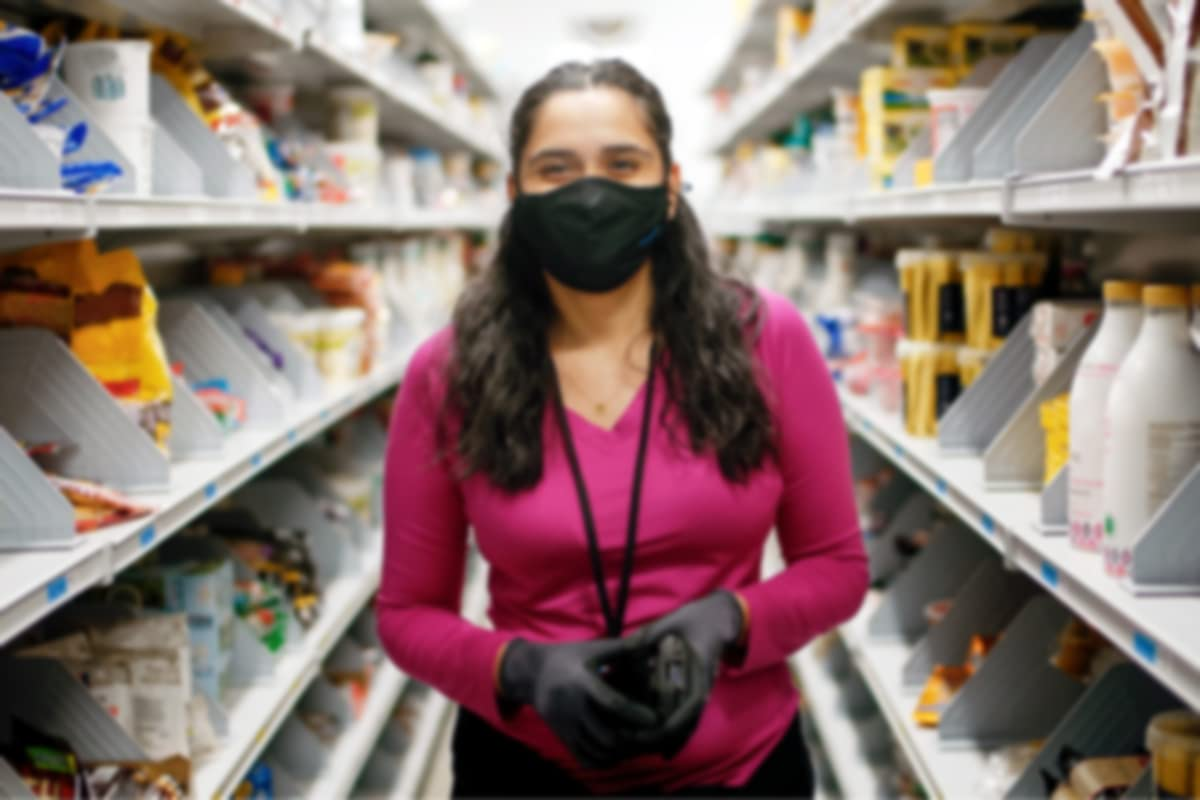 Amazon grocery warehouse associate smiling with mask