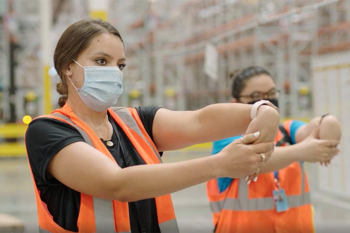 Amazon warehouse associates practicing safe stretching exercises