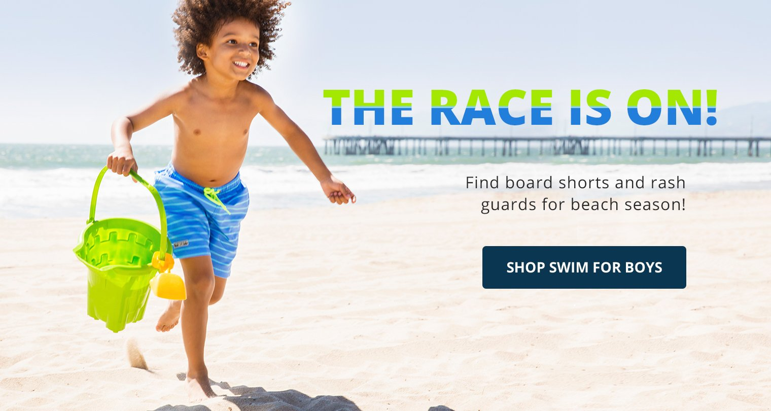 Image of a boy in board shorts playing at the beach. The race is on! Find board shorts and rash guards for beach season! Shop Swim for boys.