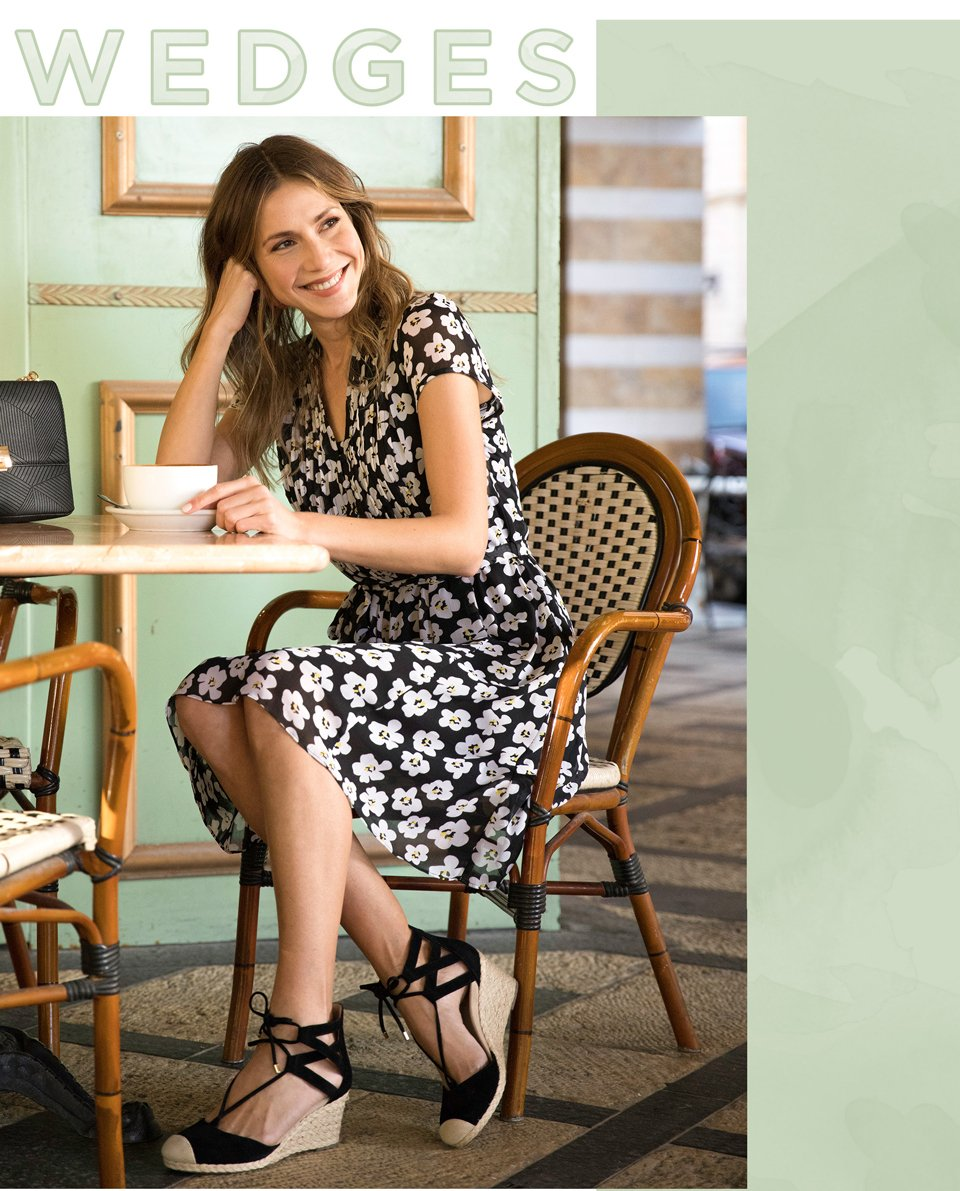 Image of a woman in a floral dress wearing a black lace up espadrille wedge made by Vionic.