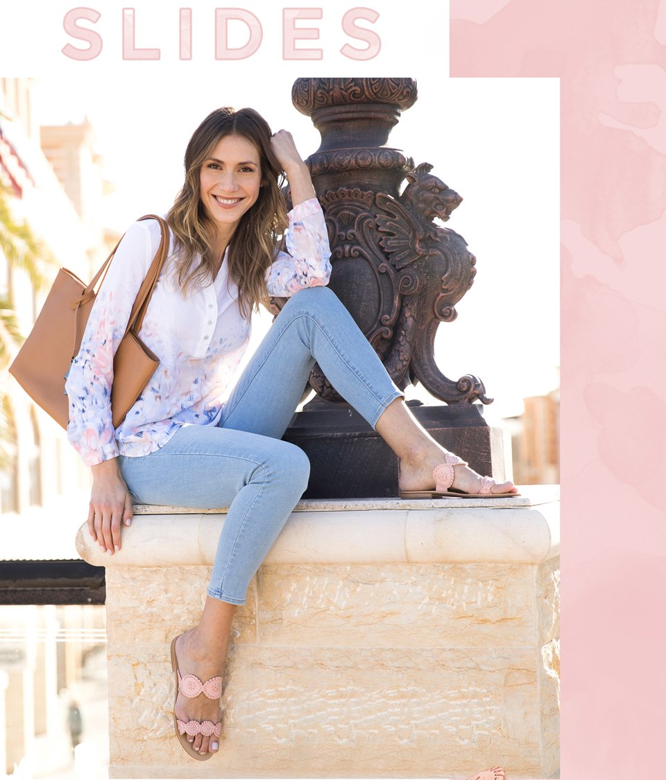 Image of a model in distressed jeans and a boho blouse wearing a pink woven slide sandal by Jack Rodgers.