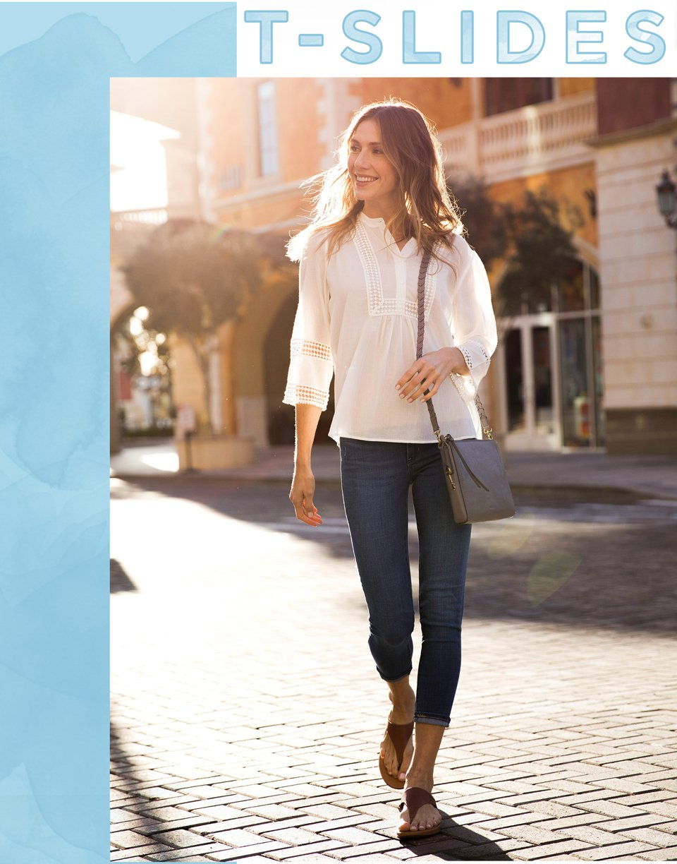 T-Slides. Image of a woman in a dark jean and peasant blouse wearing a tan leather t-strap sandal by fit flop.