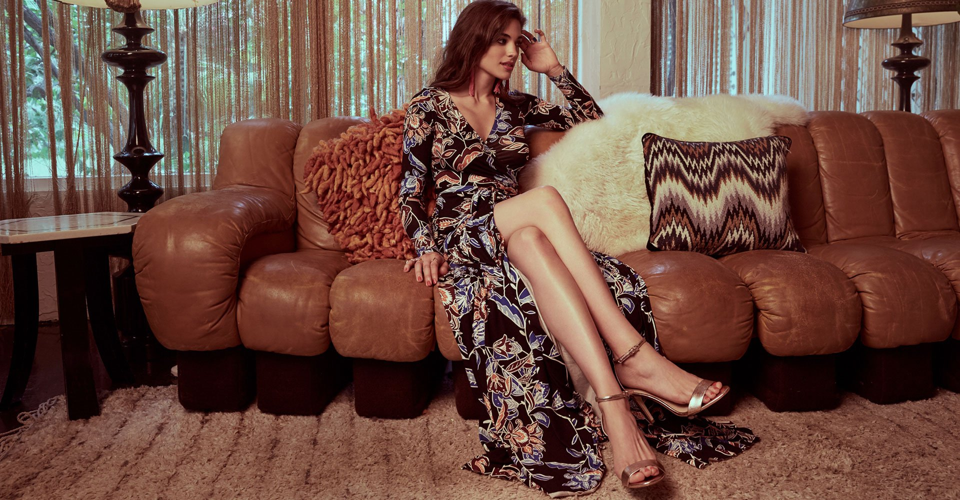 Image of a woman reclining on couch in a printed maxi dress