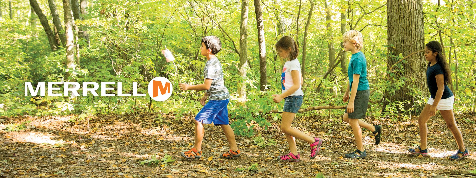 Merrell logo. Image of kids playing in the woods.