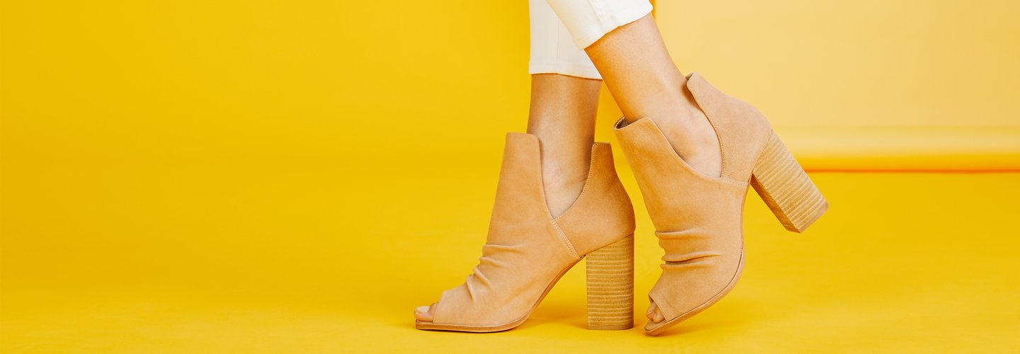 image of a suede bootie on a yellow background