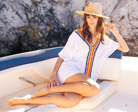 Image of  a women on a boat in a sunhat and swim coverup.