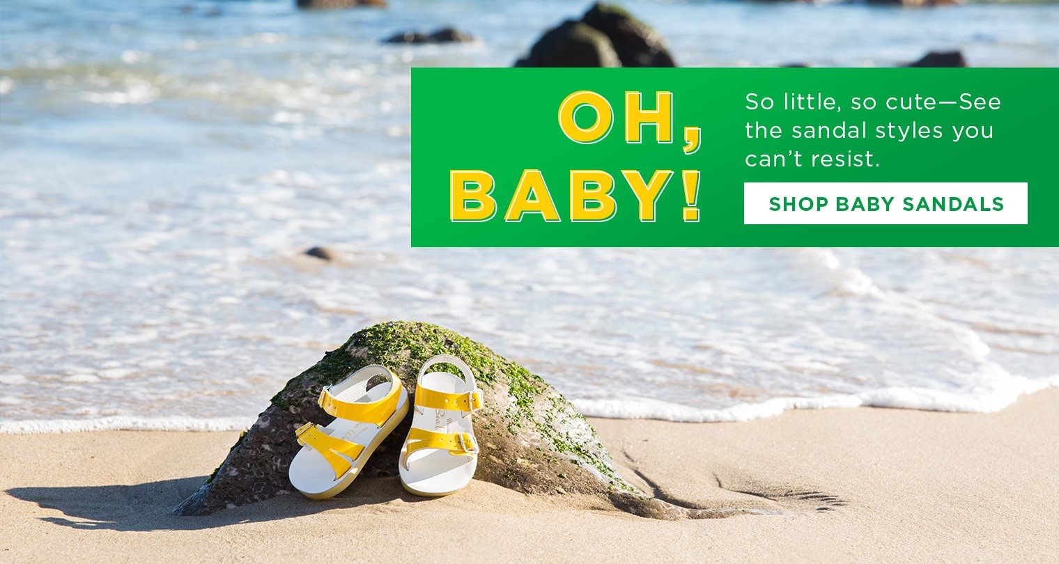 Image of baby sandals on the beach with ocean in background