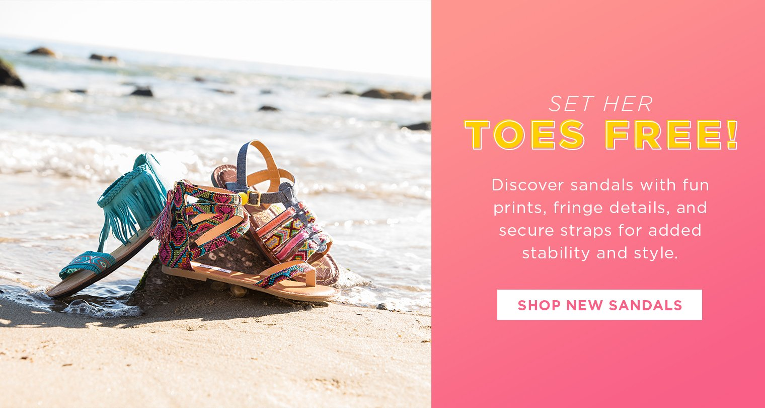 Image of girls sandals on the beach with ocean in the background