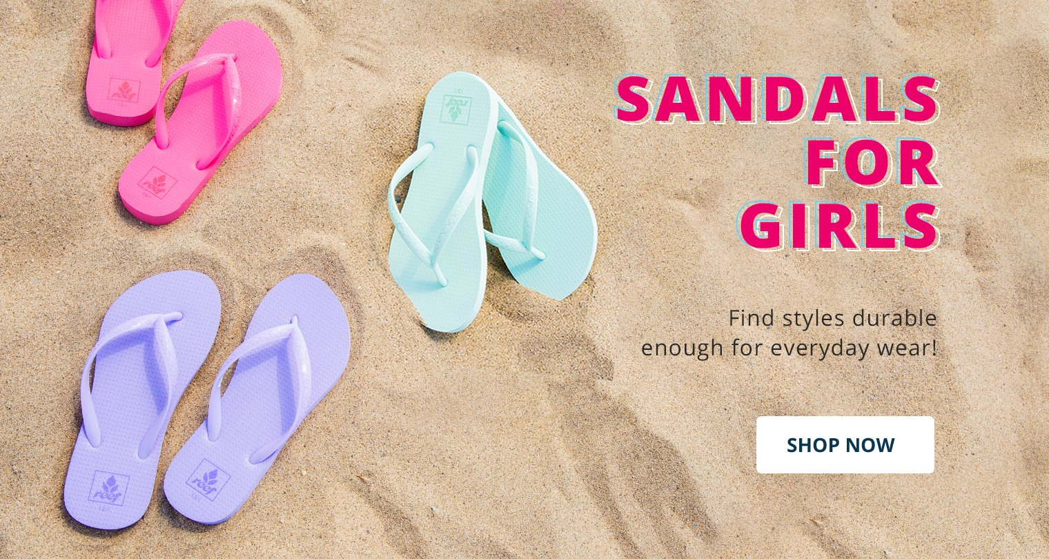 Image of girls sandals on the beach with sand in the background
