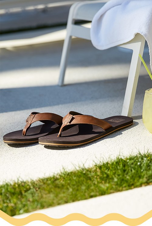 Men's flip flops beside a pool scene