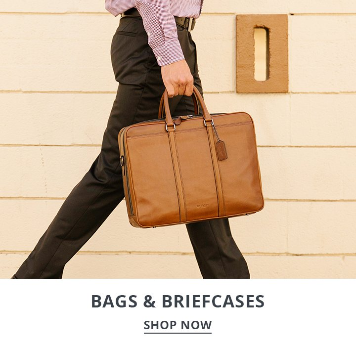 Image of a man walking on the street carrying a Coach work briefcase.