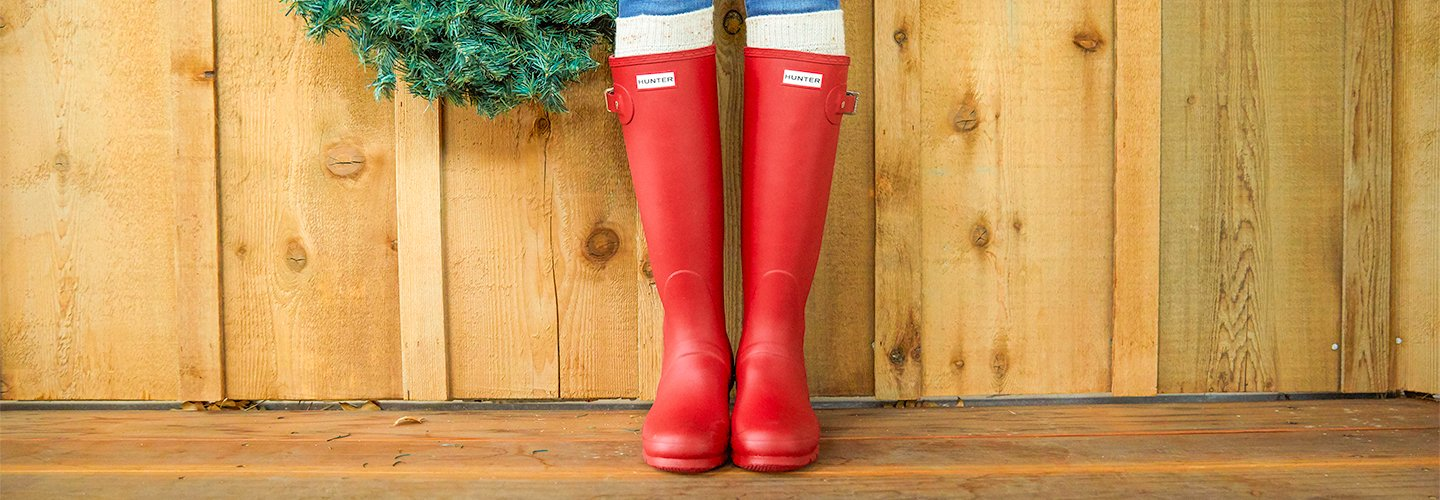 image of woman wearing hunter boots. links to selection of hunter boots.