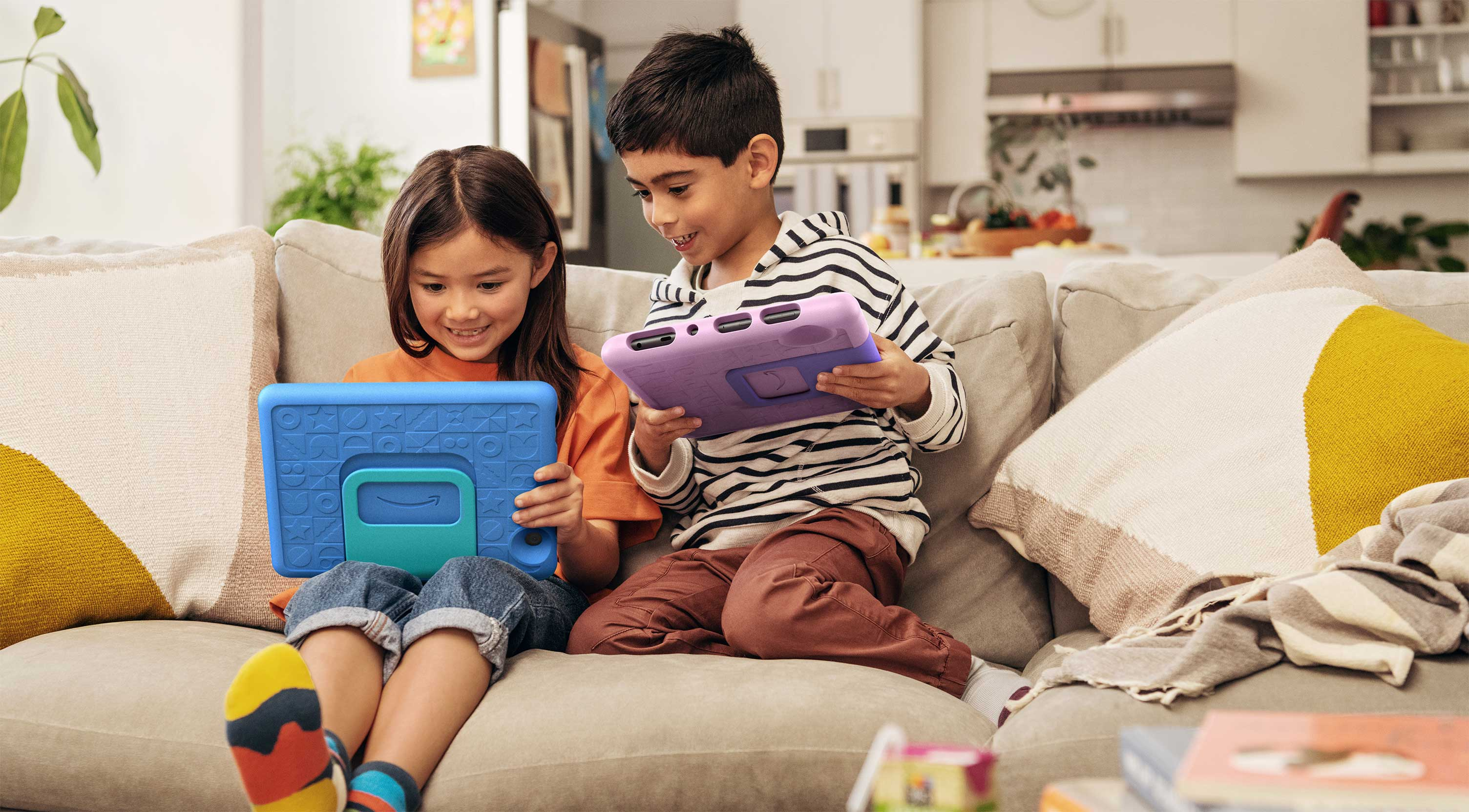 Two smiling children seated on a couch, each using their Fire HD 10 Kids tablet.