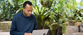 A man works on a laptop with greenery in the background.